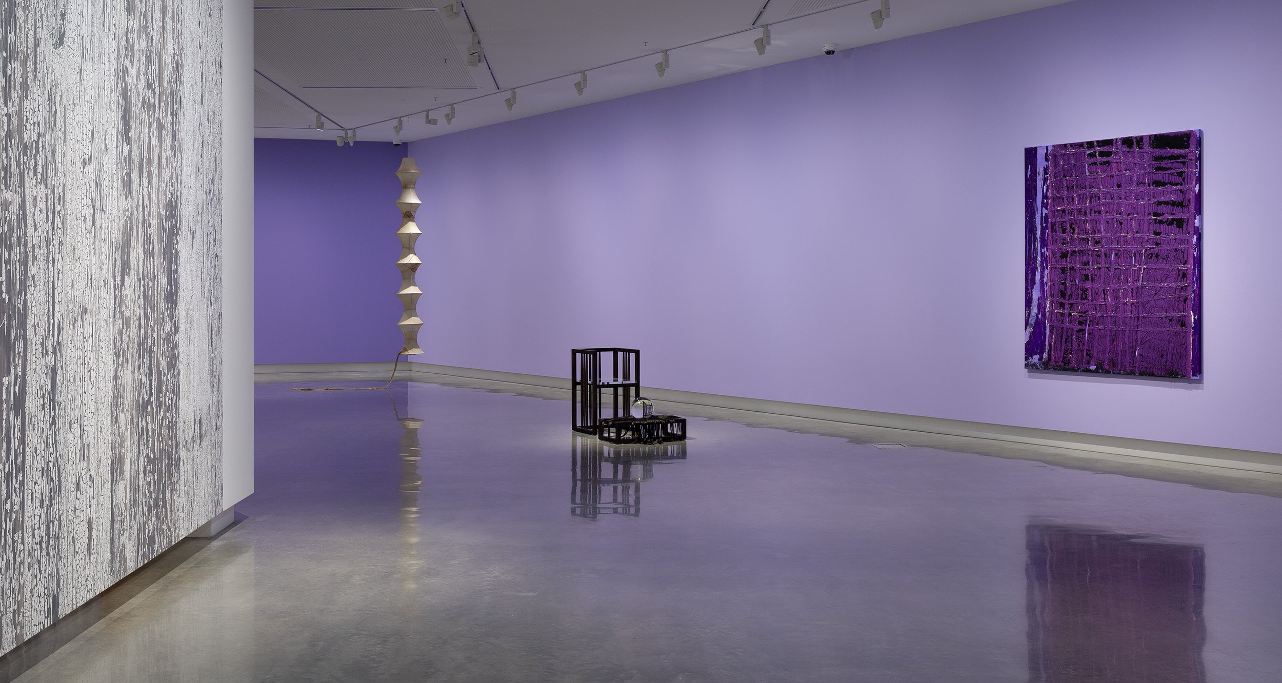 Image shows a section of the gallery with purple walls. A black chair-like installation sits on the floor, a purple painting on the wall and a hanging artwork in the background.
