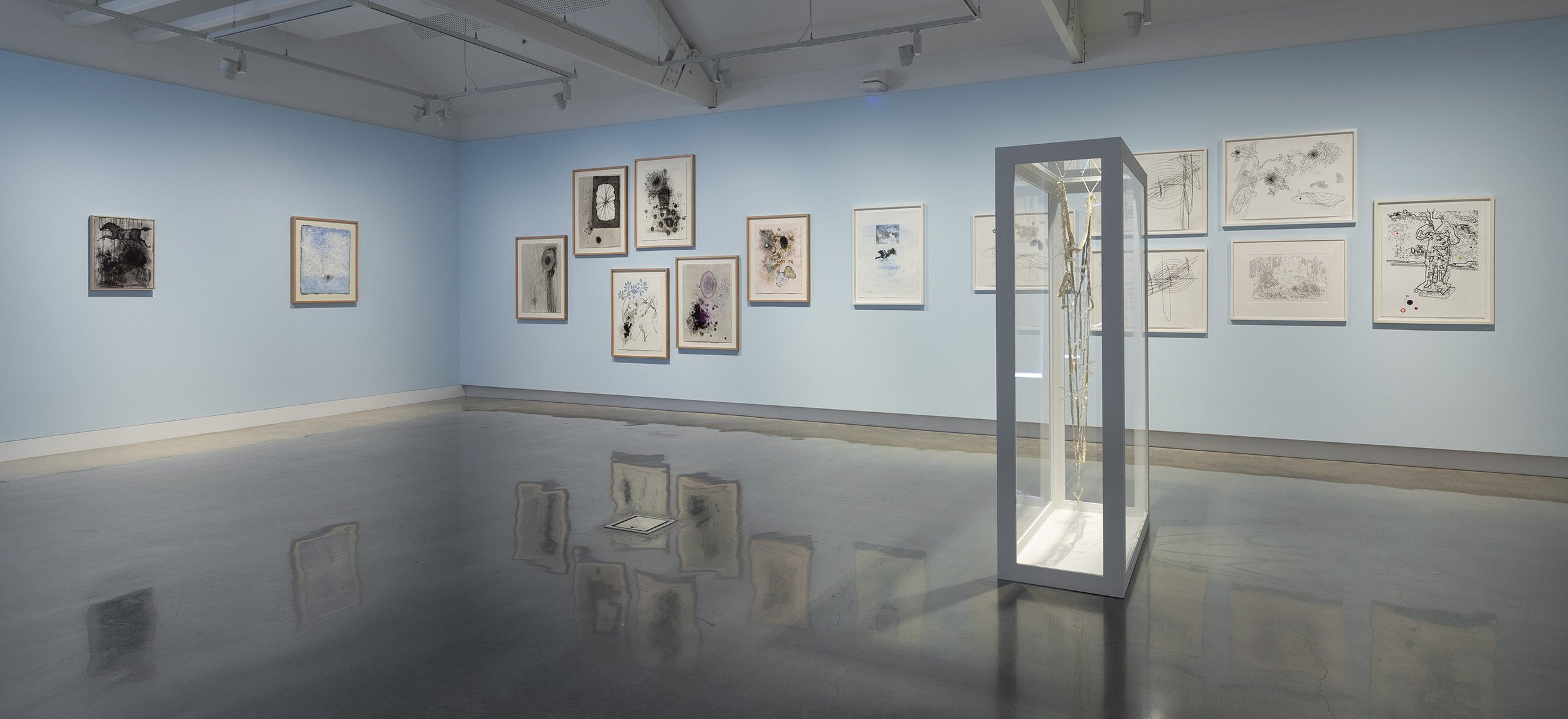 Image shows a standing 3D frame, inside which hangs a black beaded decorative artwork. Behind are other framed artworks hung on blue gallery walls.