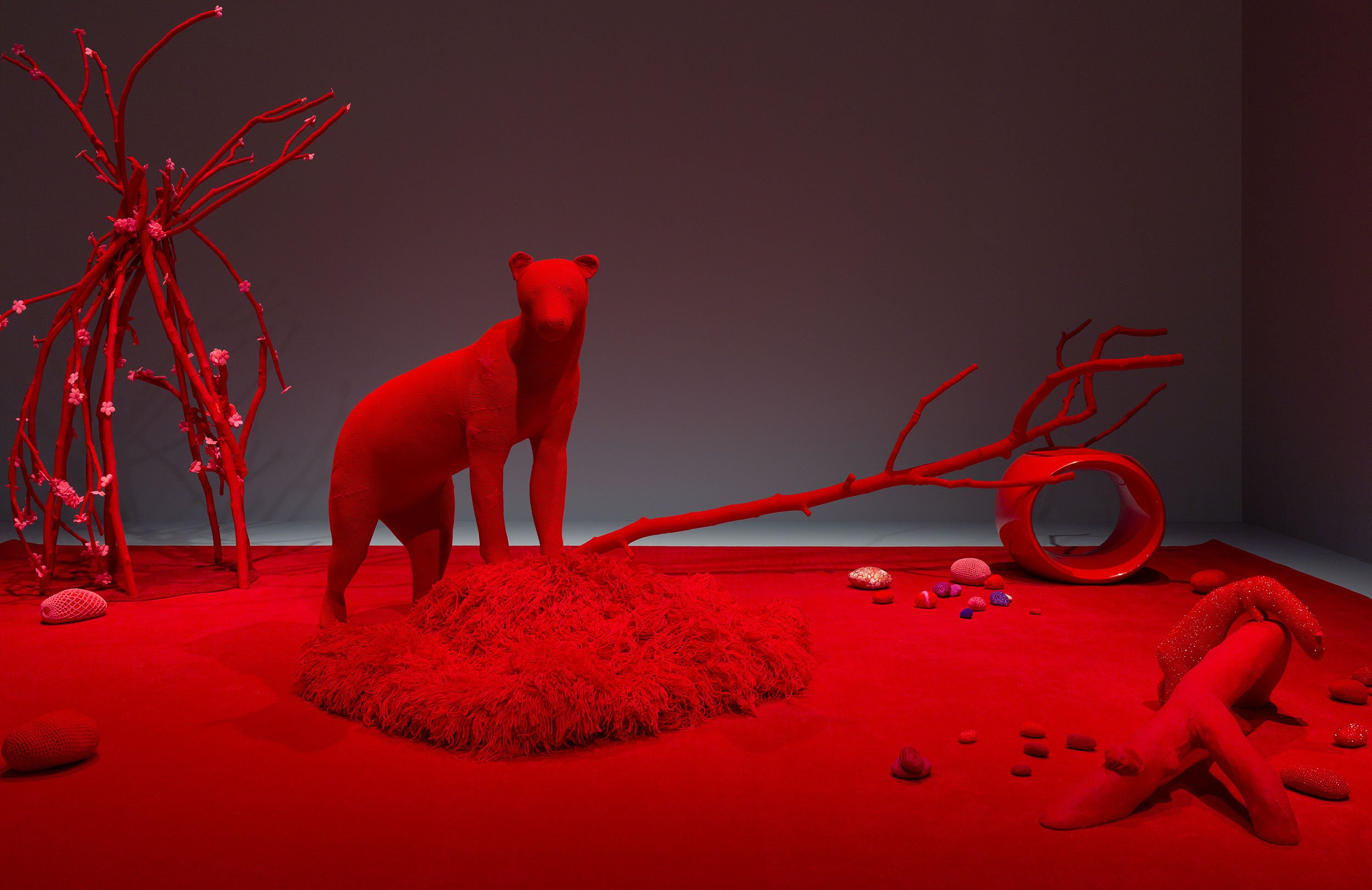 Installation artwork of a red carpet with an assortment of red crocheted objects and animals (including a bear-like creature, a squirrel and a ferret-like creature) sitting on top.